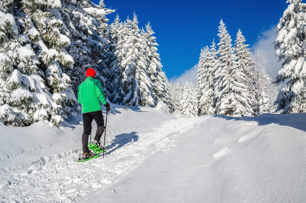 Athletic man with snow shoes on winter trail. Experience Meribel